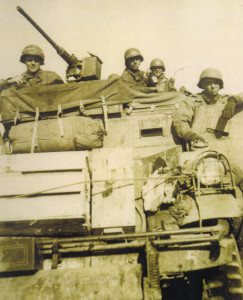 "From left to right: S/Sgt John Fague, PFC Donald E. White, PFC Dock E. Deakle, and driver of the ""BAT,"" T/5 Orvin P. Rasnic"